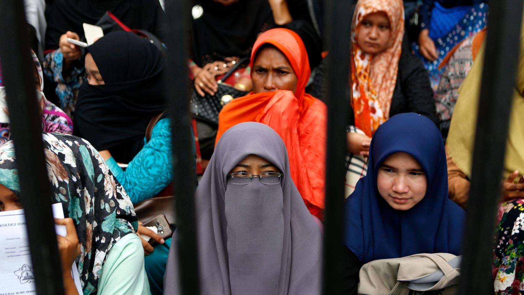 Banda Aceh, 2017. május 23. Homoszexuális viszonya miatt elítélt két férfi nyilvános megbotozását nézik muzulmán nők az indonéziai Aceh tartomány székhelyén, Banda Acehben 2017. május 23-án. Az iszlám vallási törvénykezés, a saría ellen homoszexualitásával vétő párt fejenként 85 botütésre ítélték. A botozás az Aceh tartományban alkalmazott saría egyik büntetési formája. (MTI/EPA/Hotli Simanjuntak)