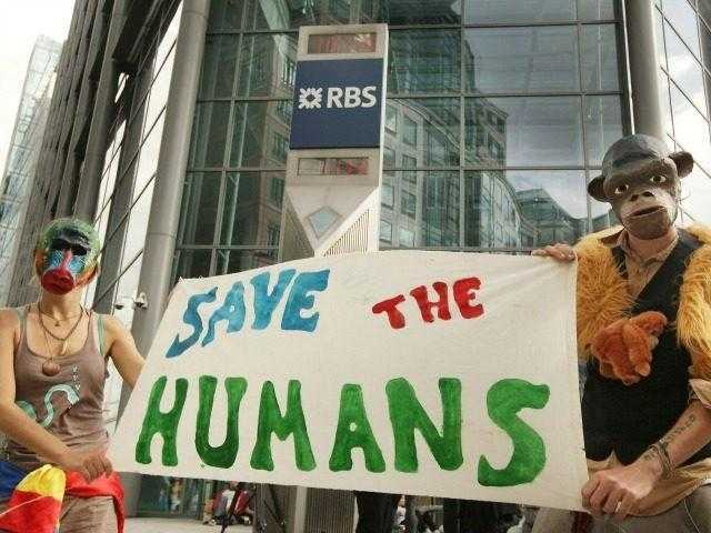 LONDON, ENGLAND - SEPTEMBER 01: Climate change protesters hold a banner as they stand at the entrance to The Royal Bank of Scotland's headquarters on September 1, 2009 in London, England. Climate campaigners have also been staging a week long protest camp in Blackheath south London. (Photo by Peter Macdiarmid/Getty …